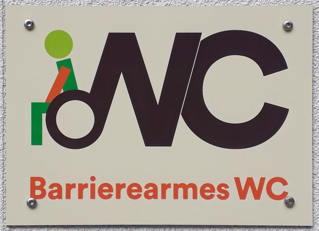Weißes Schild mit Text WC in schwarz. Darunter in rot Barrierearmes WC. Eine Linie des W von WC ist durch eine gezeichnete Person im Rollstuhl symbolisiert.