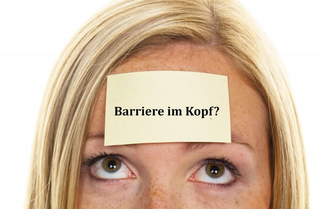 Frau mit einem Merkzettel auf der Stirn: Barriere im Kopf