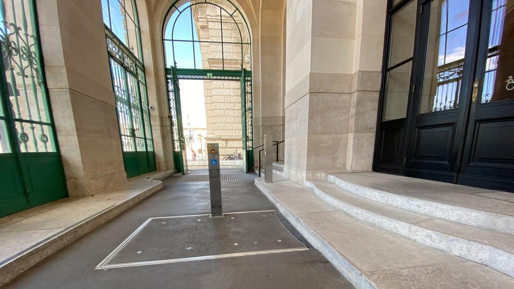 Rechts sind 3 Stufen, davor ist ein Platz mit einer Metallstele und am Boden erkennt man eine rechteckige Fläche die in den Boden eingelassen ist.