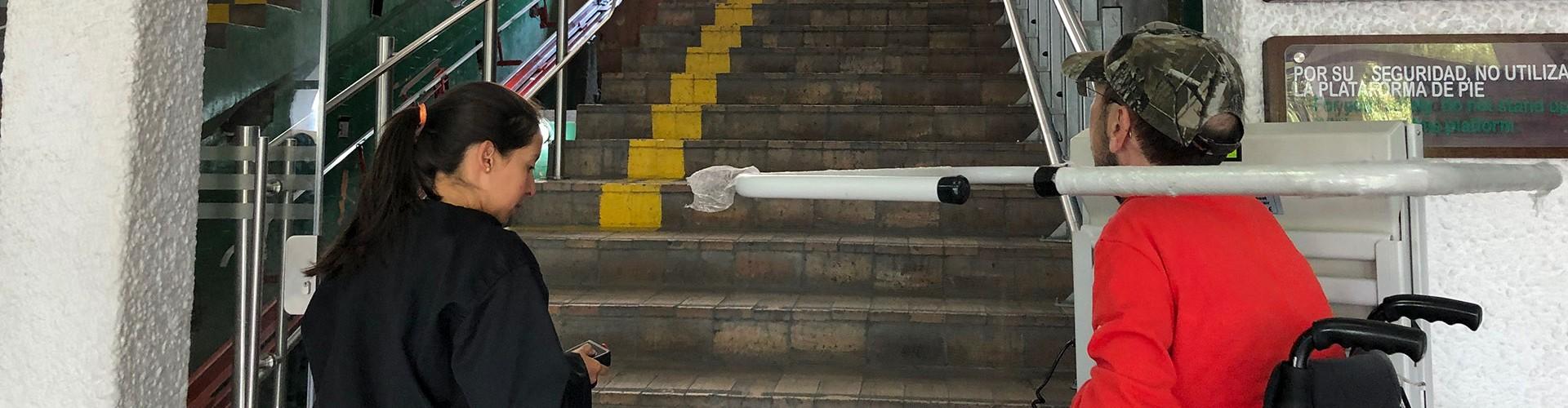 Rollstuhlfahrer auf Treppenlift am Anfang vieler Stufen nach oben, es ist eine Station einer Standseilbahn. Eine Frau steuert ihn. Am Ende der Stufen sieht man ein Rollstuhlsymbol.