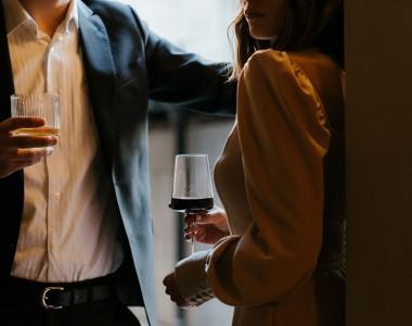 Eine Frau und ein Man stehen sich gegenüber, die Köpfe sieht man nicht wirklich, der Mann im schwarzen Anzug, links stehend, hält ein Glas mit gelber Flüssigkeit, die Frau, rechts, in weißem Kleid, rückenfrei, steht mit dem Rücken zu einer Wand, sie hält ein Weinglas mit Rotwein.