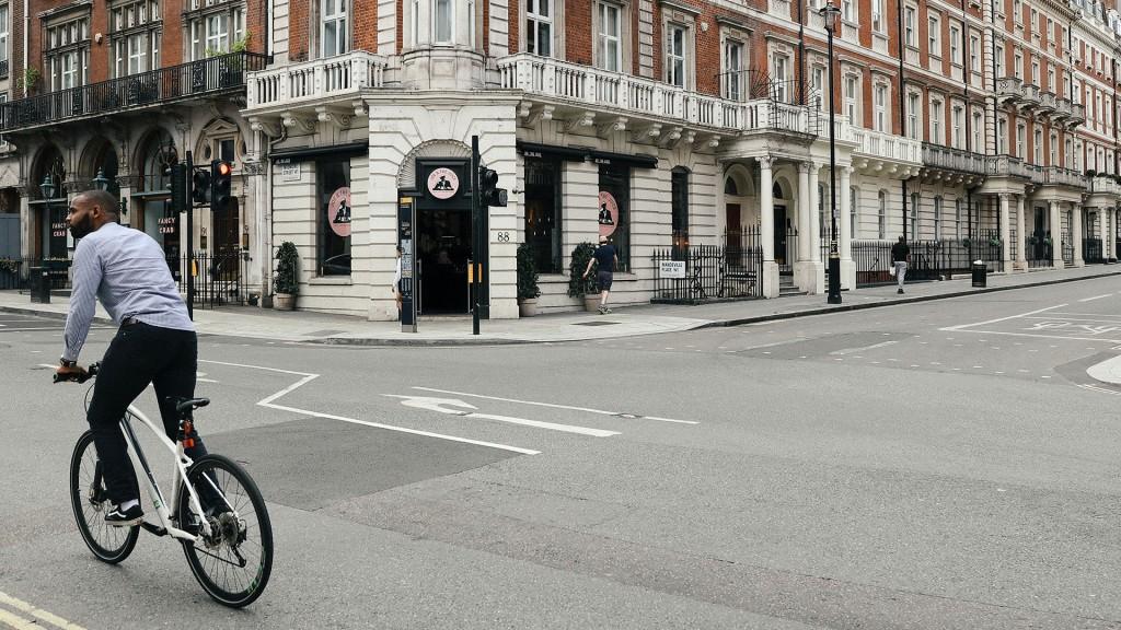 Ein schwarzer Mann mit weißem Fahrrad fährt auf einer Straße mit alten Häusern im Hintergrund nach links.