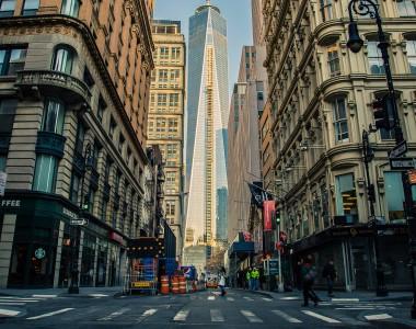 Straßenszene an einer Kreuzung in Manhattan, New York City. Links ein Starbuchs. Über jede Straße führt ein Zebrastreifen mit Gehsteigabsenkung und Aufmerksamkeitsfeld am Gehsteigrand. Im Hintergrund das neue World Trade Center.