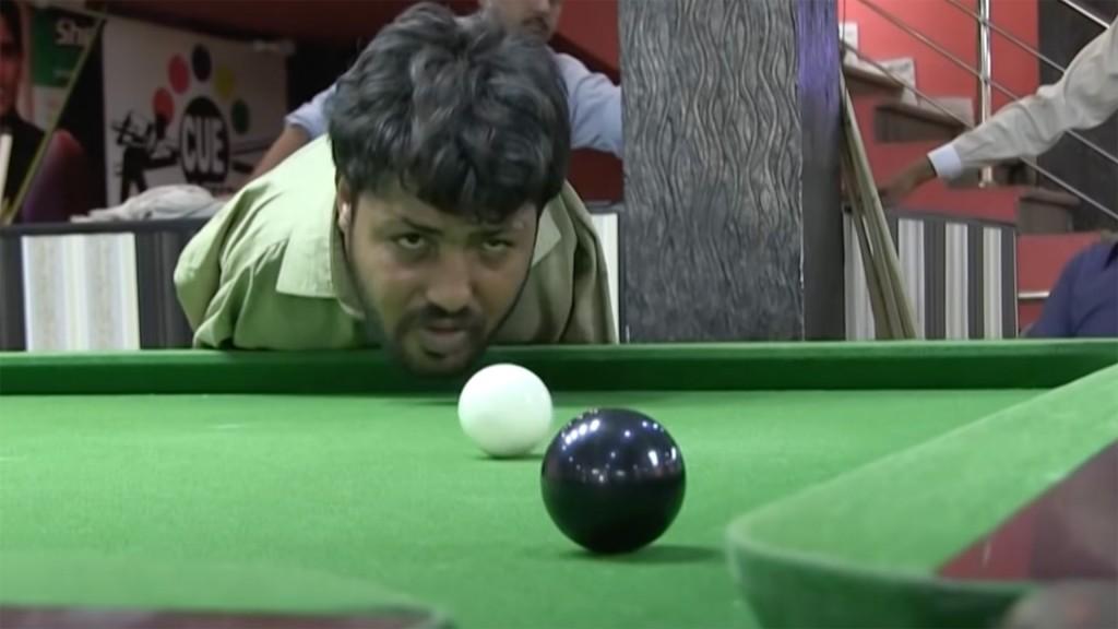 Muhammad Ikram blickt über einen Snookertisch in unsere Richtung, er überlegt wie er mit dem Kinn die weiße Kugel auf die schwarze schießen muss um sie im Loch vor uns zu versenken.