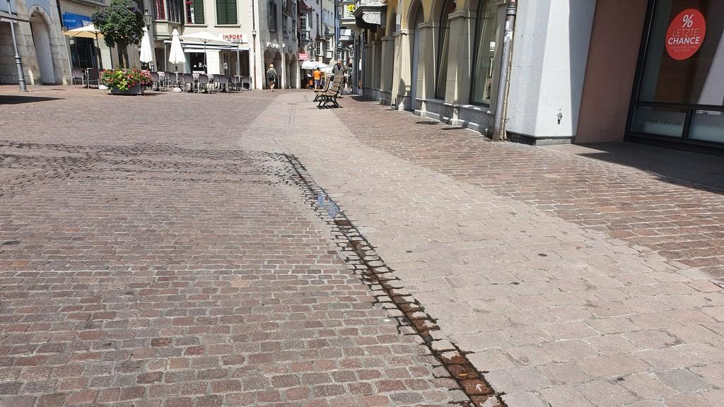 Altstadt Schaffhausen, die Straße ist rot gepflastert. Ein Streifen am Rand ist heller und sieht aus als ob er geputzt wurde.