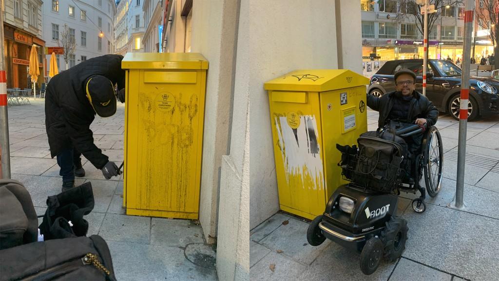 links im Bild die Seitenansicht des gelben Briefkasten, er ist ca. 1 Meter hoch. Rechts, ein Rollstuhlfahrer mit Zugmaschine mit den Rollstuhl blickt in die Kamera. Er steht beim Briefkasten und hält die Hand zum Einwurfschlitz. Links und rechts am Briefkasten gibt es Einfwurfschlitze. Der Brirefkaste ist etwa 1,1 Meter hoch und geht bis zum Boden.