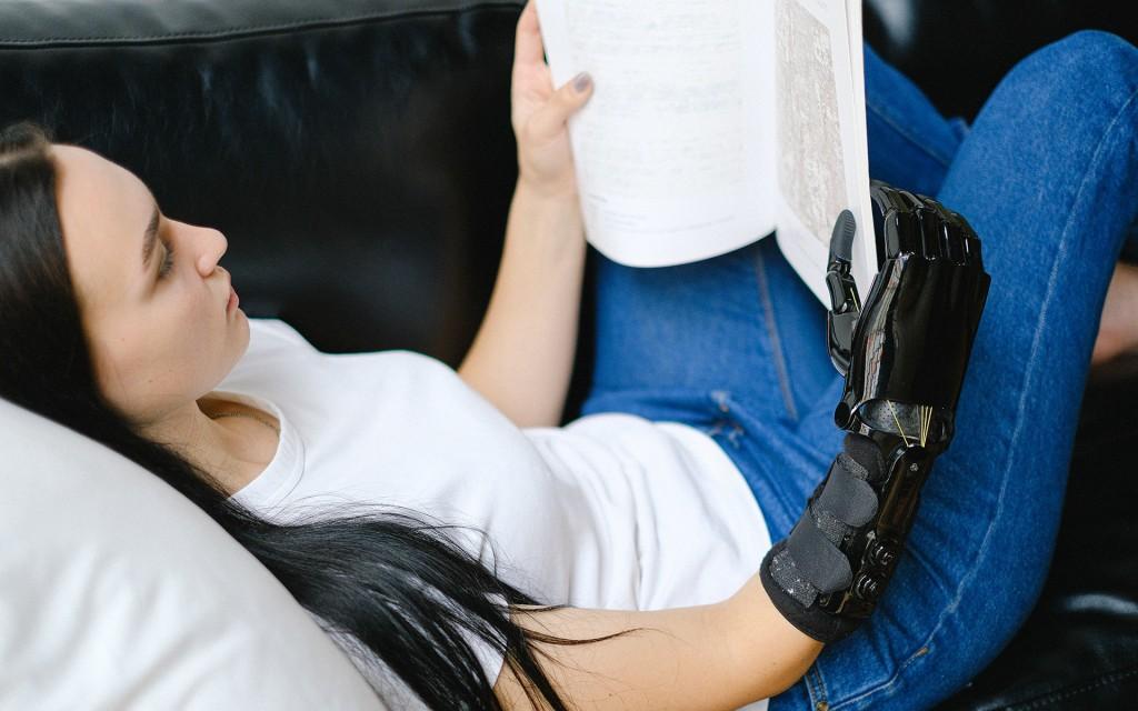 Eine Frau mit langen schwarzen Haaren und weißem Shirt, blauer Jeans liegt auf einer Couch. In der Hand hält sie ein Buch. Die rechte Hand ist eine schwarze Prothese