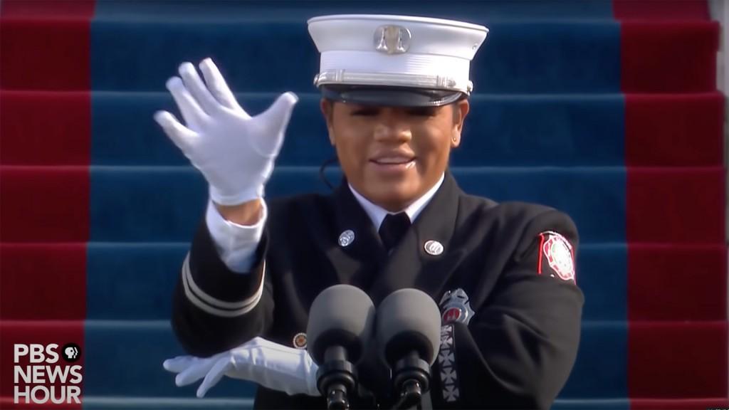 eine schwarze Frau in Uniform sieht in unsere Richtung. Ihre Hände gebärden etwas. Hinter ihr sind blaue Treppen erkennbar.