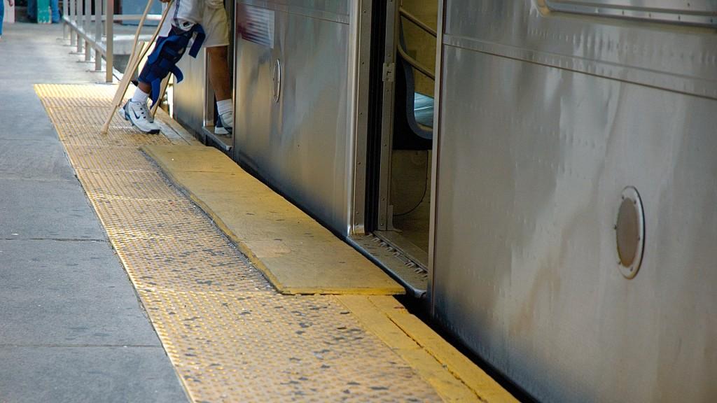 Ein U-Bahn-Steig, ein breiter gelber Aufmerksamkeitsstreifen mit erhabenen Punkten. ein teilweise darüber montiertes gelbes Holzbrett verringert den Spalt beim Einstieg in den U-Bahn-Waggon