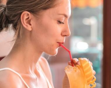 Frau trinkt mit Plastikstrohhalm