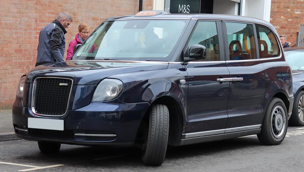 Seitenansicht eines blauen London Taxi LEVC TX, das bei einem Gehsteig parkt.