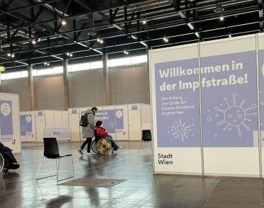 Ein Schild: Willkommen in der Impfstraße - Der Anfang vom Ende der Corona-Pandemie beginnt hier. 2 Frauen im Rollstuhl mit Begleitpersonen stehen und warten in einer großen Halle.
