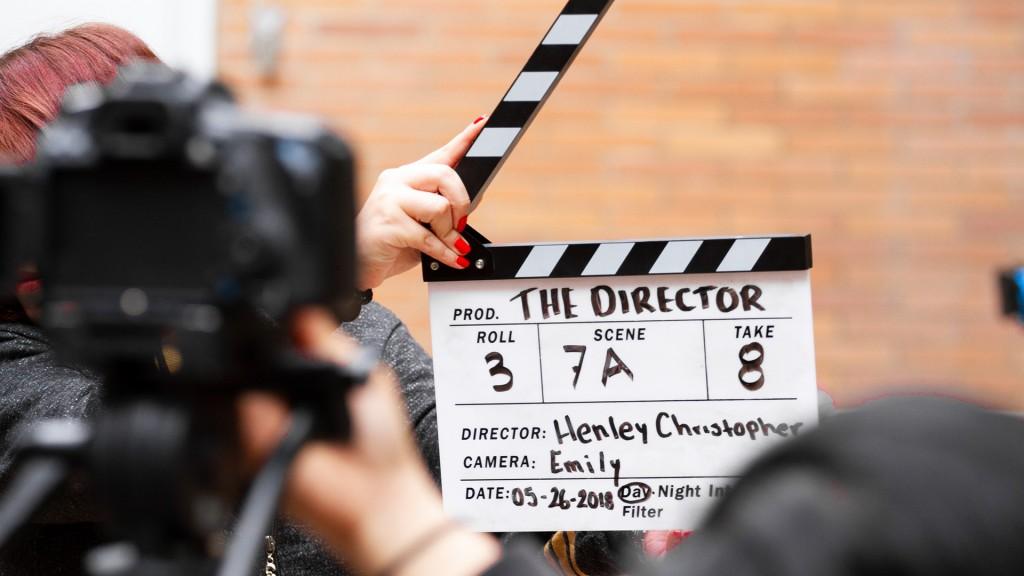 Eine schwarz/weiße Filmklappe mit Text THE DIRECTOR Roll 3 Scene 7A Take 8 Director Henley Christopher Camera: Emily Date: 05-26-2018 Day