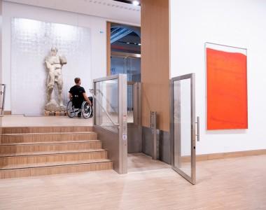 Ein helles Museum. In der Mitte ein Rollstuhhublift, die Tür zur Plattform steht offen. Links davon 5 Stufen. Oben sieht man einen Mann im Rollstuhl im Ausstellungsraum. Der Lift ist aus silbernem Metall mit großen Glasflächen vorne hinten und an der Seite. Rechts davon ein oranges Gemälde.