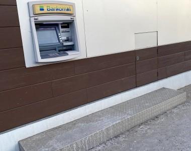 Ein Bankomat an bzw. in einer braunen Hauswand montiert in einem weißen Streifen. Am Boden ist ein Podest aus Riffelblech.