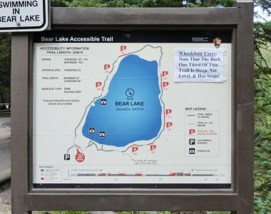 Am Anfang eines Wanderwegs eine große Karte in Holzrahmen: Bear Lake Accessible Trail. Der Weg führt um den Bear Lake in der Höhe von 9475 ft. Restliche Beschreibung im Text.