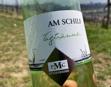 Eine Weinflasche, im Hintergrund sind Weinberge. Von der Flasche sieht man nur den Teil mit dem Etikett, darauf steht: AM SCHILF, darunter auch in Brailleschrift. Nochmals darunter steht in grün Tagträumer und das Logo PMC Münzenrieder. Links davon ein gezeichneter Reiher.