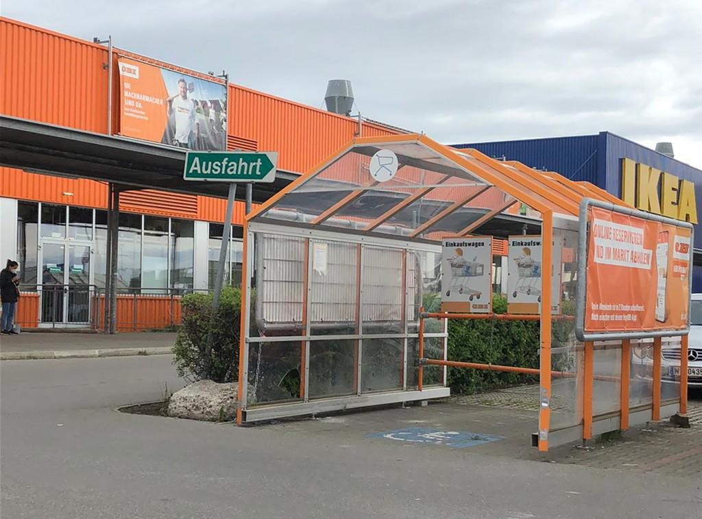 Auf einem Obiparkplatz sieht man am Boden ein Rollstuhlsymbol. Der Parkplatz ist aber überdacht mit einem orangen Metallgerüst und beschriftet für Einkaufswagen. Derzeit steht kein Einkaufswagen drinnen. Im Hintergrund sind die Gebäude von Obi und IKEA erkennbar.