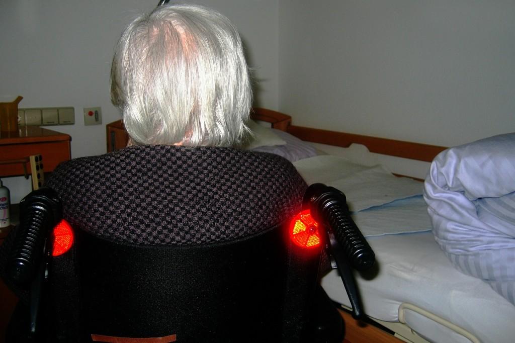 Alte Frau im Rollstuhl im Pflegeheim. Wir sehen sie von hinten (weiße Haare), rechts von ihr ein Bett.