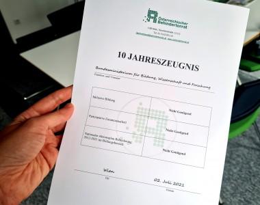 Man sieht ein Blatt Papier, welches wie ein Zeugnis vom Österreichischen Behindertenrat an das Bildungsministerium aussieht. Die Fächer lauten: Inklusive Bildung, Partizipative Zusammenarbeit, Nationaler Aktionsplan 2012-2021 im Bildungsbereich. Alle drei Fächer sind mit Nicht Genügend bewertet. Als Datum steht unten 2. Juli 2021