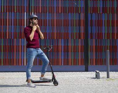 Ein Mann in blauer Jeans und rotem Pullover steht mit einem Bein auf einem E-Scooter und schnallt sich gerade den Sturzhelm an. Der Untergrund ist kleine Pflastersteine, der Hintergrund eine Hauswand aus lauter bunten Streifen.