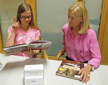 Die Generaldirektorin der Nationalbibliothek, Dr. Johanna Rachinger, und ein Mädchen sitzen uns gegenüber bei einem Tisch. Beide sind rosa gekleidet. Vor der Generaldirektorin lieg das Buch Mythos Pferd. Im Bild Vordergrund liegt eine weiße Schachtel mit der Aufschrift OrCam MyEye 2. Links von der Generaldirektorin sitzt ein Mädchen mit der Orcam MyEye2 am Brillenbügel, sie hält den Zeigefinger in die Höhe und schaut auf das Buch Pferde Geschichte, dass sie in der linken Hand hält.