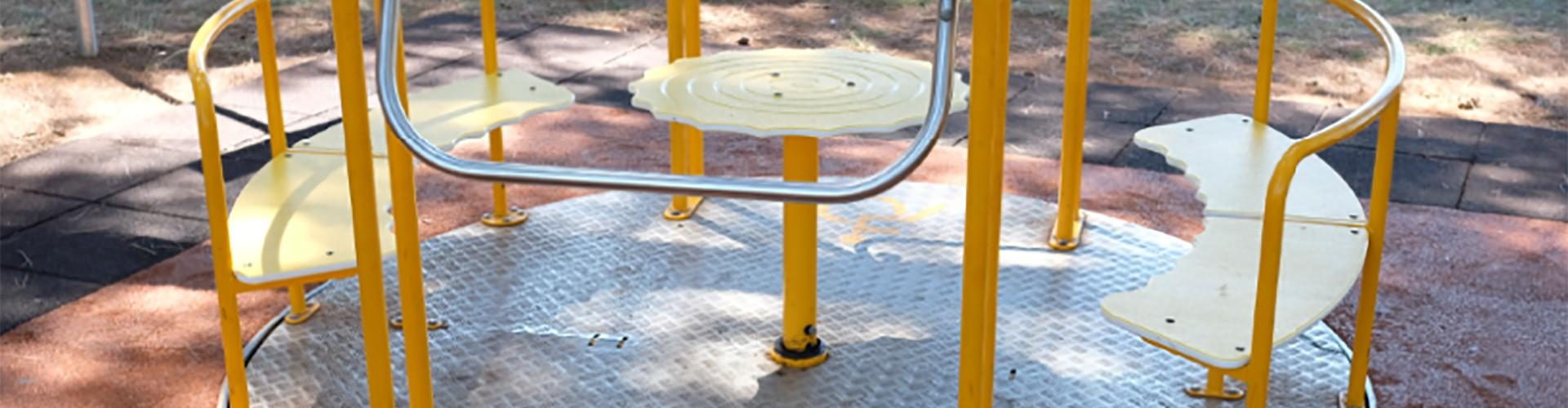 Ein gelbes Kinderkarussell. Der Boden ist Riffelblech. Vor uns und auf der Hinterseite ist ein Rollstuhlplatz, zurückgehalten werden die Rollstühle durch Metallbügel.