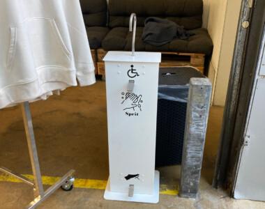Eine weiße, hüfthohe Box. Es ist der Desinfektionsspender. Oben ein Hahn wo die Flüssigkeit herauskommt, unten ein Fußpedal. In der Mitte ein Handpedal mit einem Rollstuhlsymbol beschriftet.