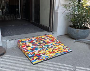 Eine bunte Legorampe bei einem Geschäftseingang. Sie überwindet 1 Stufe. Sie liegt teilweise am taktile Leitsystem. Ein Ständer steht auch am Leitsystem.