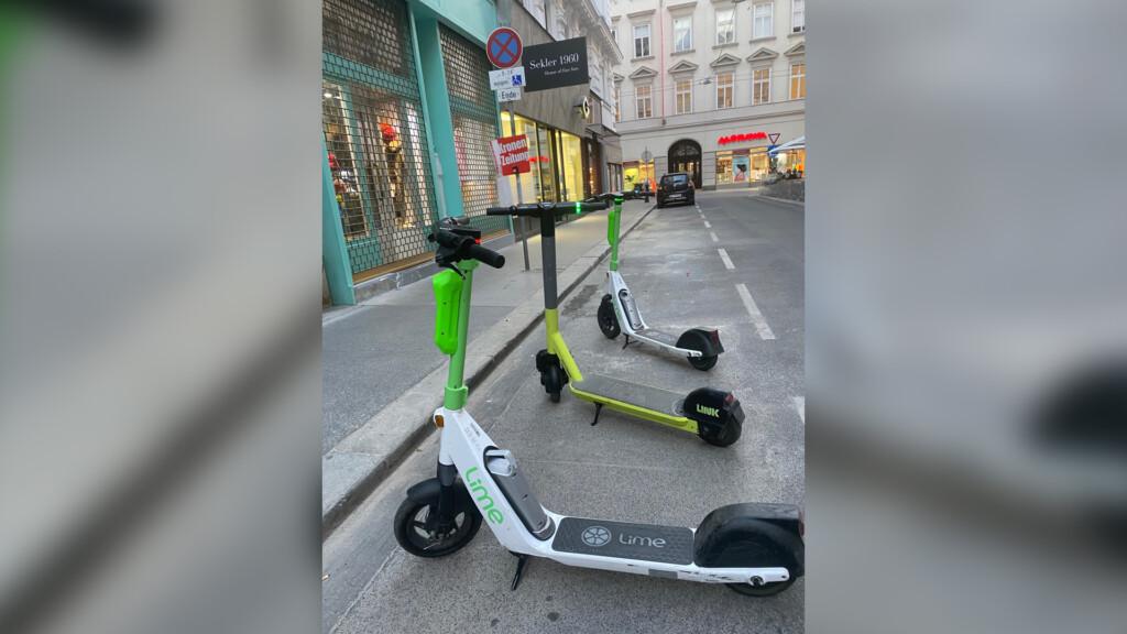 3 Scooter, 2 von Lime einer von Link, stehen schön aufgereiht auf einem Behindertenparkplatz in einer schmalen Gasse.