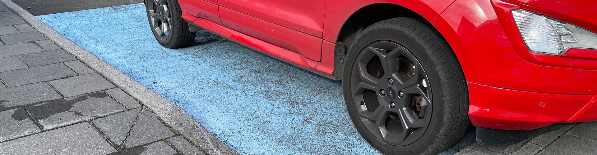 Ein kleines, rotes Auto steht auf einem blauen Behindertenparkplatz. Vorne steht es mit der Motorhaube über den Gehsteig, hinten schließt es bündig ab. Daneben ist die Rampe auf den Gehsteig, die nicht genutzt werden kann, weil das Auto genau dort steht.