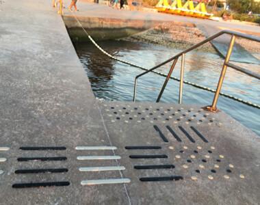 Im Vordergrund führt ein taktiles Leitsystem zu Stufen und einem Handlauf. Am Ende der Treppe ist man bereits im Meer. Im Hintergrund sieht man auch eine Rampe die ins Meer führt.