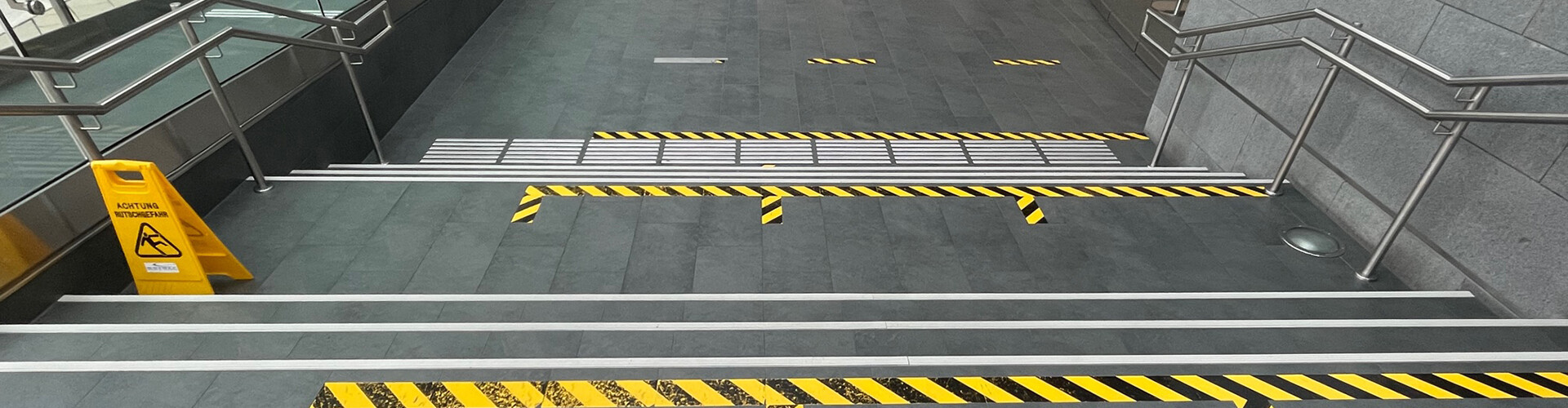 Mehrere Stufen. Direkt vor uns quer zu uns ein weißes taktiles Leitsystem. Dann gelbschwarze Streifen, dann ein weißer Streifen. Danach erst die erste Stufe. Dann wieder zwei weiße Streifen mit je einer Stufe, dann wieder gelbschwarze Streifen, dann wieder weiß, dann drei Stufen mit je einem weißen Streifen. Dann eine taktile Auffanglinie, dann ein gelbschwarzer Streifen. Jetzt hat man die sechs Stufen überwunden.